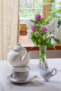 Teapot teacup and milk jug lilacs in a glass vase Royalty Free Stock Image