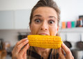 Teasing, happy woman taking big bite of corn on the cob Royalty Free Stock Photo