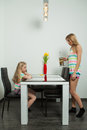 Teatime at home mother and daughter have red cups yellow tulips Stock Photos
