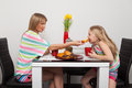 Teatime at home mother and daughter have red cups yellow tulips Stock Photo