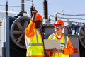 Technical workers discussing work at electrical substation Royalty Free Stock Photography