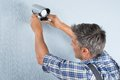 Technician adjusting cctv camera close up of a on wall Royalty Free Stock Image