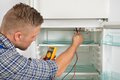 Technician Checking Fridge With Multimeter Royalty Free Stock Photo