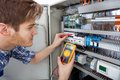 Technician examining fusebox with insulation resistance tester side view of male digital Royalty Free Stock Photo