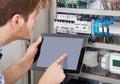Technician examining fusebox using tablet Royalty Free Stock Photo