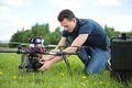 Technician fixing camera on uav helicopter young in park Royalty Free Stock Images