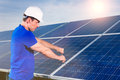 Technician maintaining solar panels photovoltaic system with for the production of renewable energy through energy a using a Stock Images