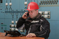 Technician make mobile phone call in the power plant control cen
