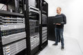 It technician monitors data center engineer or consultant standing with a laptop and monitor blade servers in rack shot in Royalty Free Stock Image