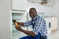 Technician repairing refrigerator appliance happy african in kitchen room Stock Photography