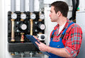 Technician servicing heating boiler the gas for hot water and Royalty Free Stock Photo