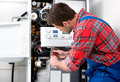 Technician servicing heating boiler the gas for hot water and Stock Photography