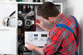 Technician servicing heating boiler the gas for hot water and Stock Photos