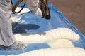 Technician spraying foam insulation using Plural Component Spray Gun.