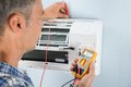 Technician testing air conditioner portrait of a mid adult male with digital multimeter Stock Images