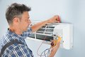 Technician testing air conditioner portrait of a mid adult male with digital multimeter Stock Photography