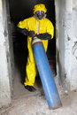 Technician in uniform with steel cylinder yellow protective mask and gloves dealing gas Stock Photos