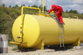 Technician working on large fuel tank in red uniform and hard hat Stock Photo
