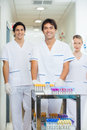 Technicians with medical cart in hospital corridor portrait of confident lab Stock Images
