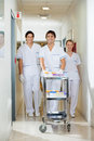 Technicians with medical cart walking in corridor portrait of confident lab hospital Royalty Free Stock Photo