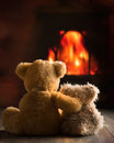 Teddies by the fire two teddy bears sitting Royalty Free Stock Image
