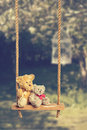 Teddies on rustic swing two in the orchard with vintage tone effect Royalty Free Stock Photography