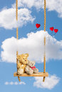 Teddies on swing two teddie bears sitting rustic wooden rope Stock Photo