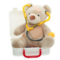 Teddy bear with bandages and child medical kit sitting in a wearing a stethoscope to play doctor open full of supplies toys in Royalty Free Stock Photo