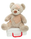 Teddy bear with bandages and child medical kit to play doctor open full of supplies toys in primary colors red blue yellow Stock Photo