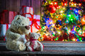 Teddy bear and christmas tree with presents on background old wooden table Royalty Free Stock Photo