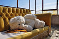 Teddy bear and couch in abandoned building vintage social issues Stock Photo