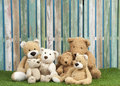 Teddy bear family group of bears seated on grass against a fencr Royalty Free Stock Photography