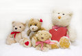 Teddy bear family mother with children and red heart of wood f four teddybear for christmas decoration a heard a checked ribbon Royalty Free Stock Photography