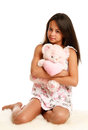 Teddy bear girl in pajamas with a pink sitting on white fur Stock Photo