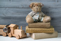 Teddy bear in glasses on the old books and wooden toy train