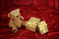 Teddy bear with golden gift box on red Royalty Free Stock Photo