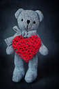 Teddy bear holding a heart on a black background Stock Photos