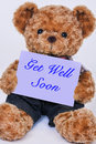 Teddy bear holding a purple sign that says Get Well Soon Royalty Free Stock Photo