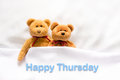 Teddy Bear lying in the white bed with message Happy Thursday Royalty Free Stock Photo