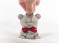 Teddy bear money box depositing a coin into a child s Royalty Free Stock Images