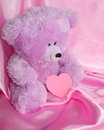 Teddy bear and pink heart on purple stock photos silk background holiday card for valentines day or for fathers mothers day Royalty Free Stock Photo