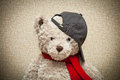 Teddy bear in a red scarf and a black baseball cap