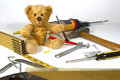 Teddy bear repairman sitting amid home repair maintenance construction tools Royalty Free Stock Photography
