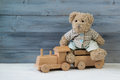 Teddy bear sitting on the toy wooden train, wooden background