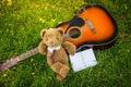 Teddy bear sleep on classical guitar on field. Royalty Free Stock Photo