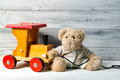 Teddy bear and toy wooden train, wooden background