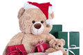 Teddy bear wearing christmas hat with gifts isolated on white ba background Royalty Free Stock Photo