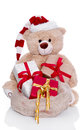 Teddy bear wearing christmas hat with gifts isolated on white ba gift boxes as a santa claus a background Royalty Free Stock Photo