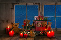 Teddy bears and red candles decorated on an old windowsill backg background with view out in the nigth Stock Photo