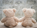 Teddybears holding hands photo taken from behind Stock Photo